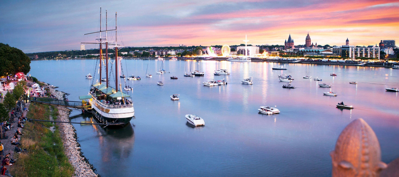 Der Sonnenuntergang über dem Rhein in Mainz, wo einige Boote friedlich schwimmen, Rheinhessen
