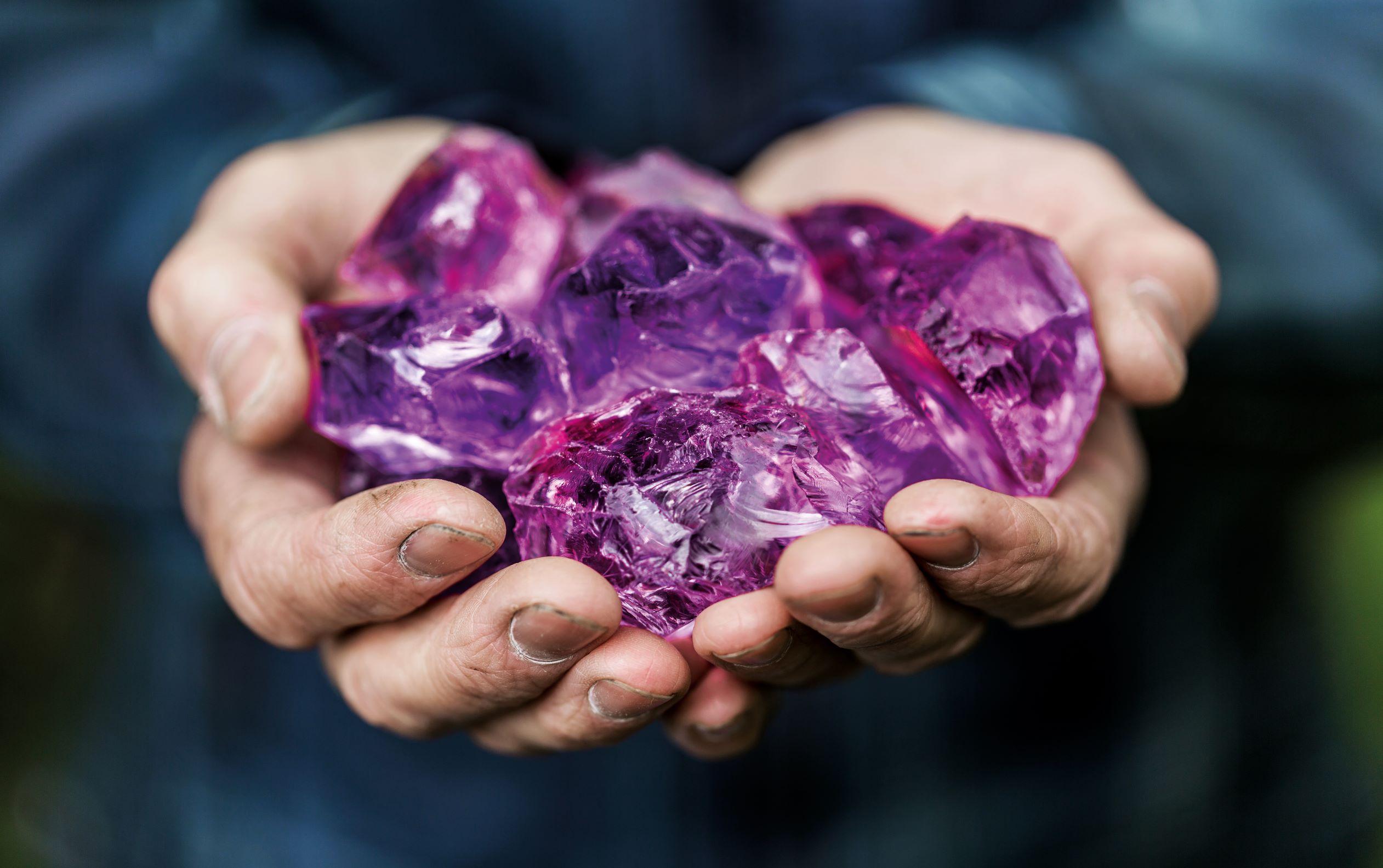Die Hände eines Edelsteinschleifers halten kostbare Aquamarine, EdelSteinLand