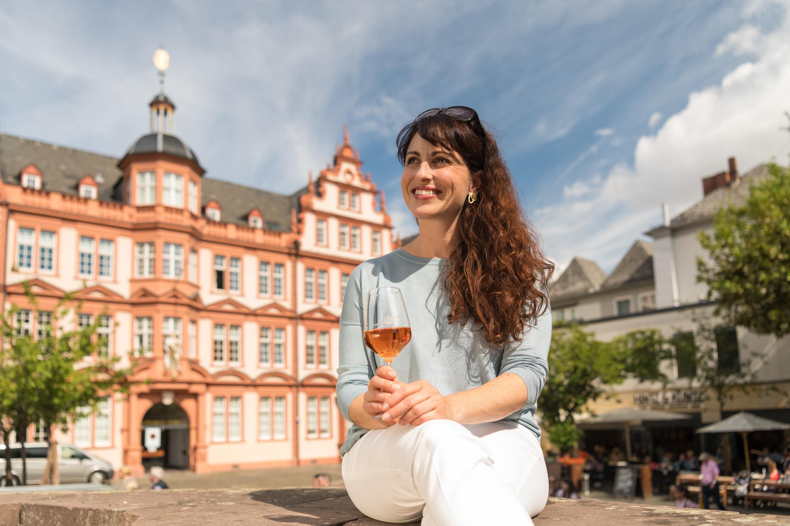 Eine Touristin genießt Wein vor dem Gutenbergmuseum in Mainz, Rheinhessen