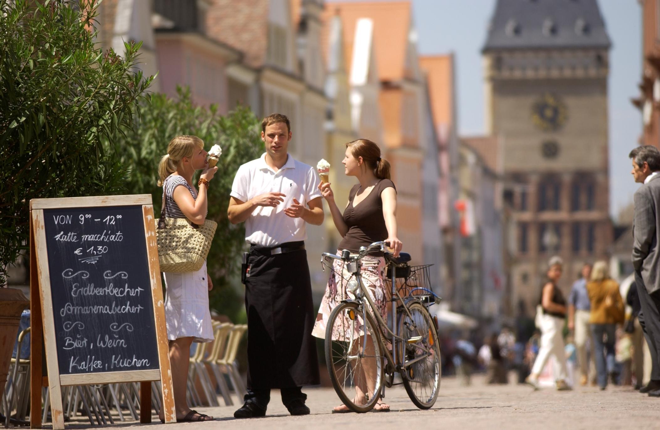 Passanten genießen ein Eis in der Maximilianstraße in Speyer, Pfalz